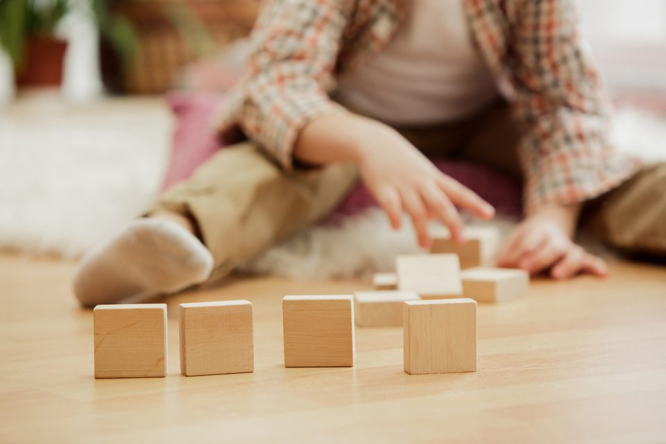 little-child-sitting-on-the-floor-pretty-boy-palying-with-wooden-cubes-at-home